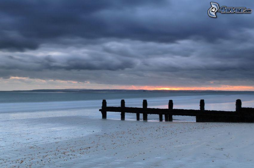 drewniane molo, morze, plaża, ciemne chmury nad morzem