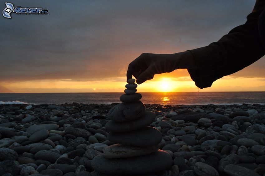 kamienista plaża, Zachód słońca nad morzem, ręka