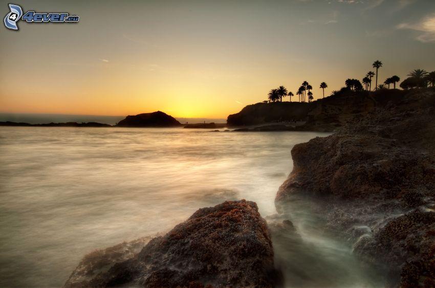 kamieniste nadbrzeże, morze, niebo o zmroku