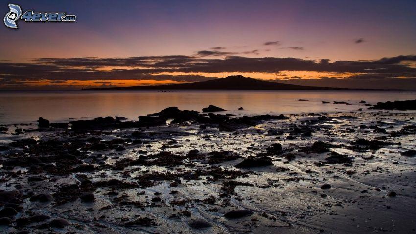 morze, kamienista plaża, niebo o zmroku