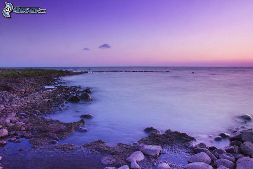 morze otwarte, fioletowe niebo, skalisty brzeg