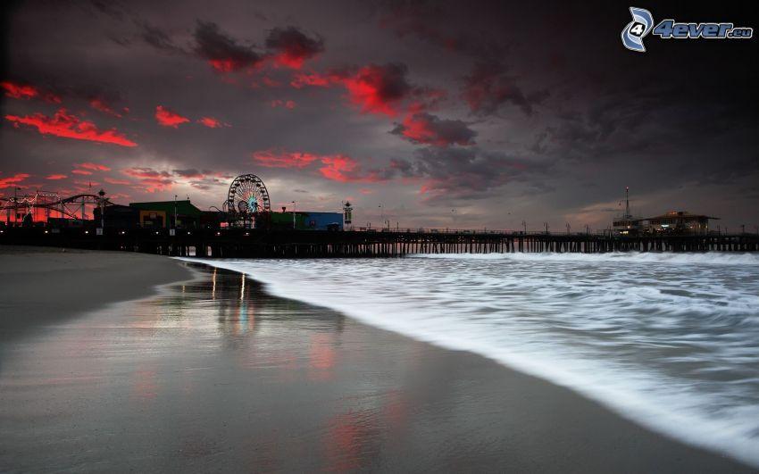 plaża piaszczysta, drewniane molo, karuzela, wieczór