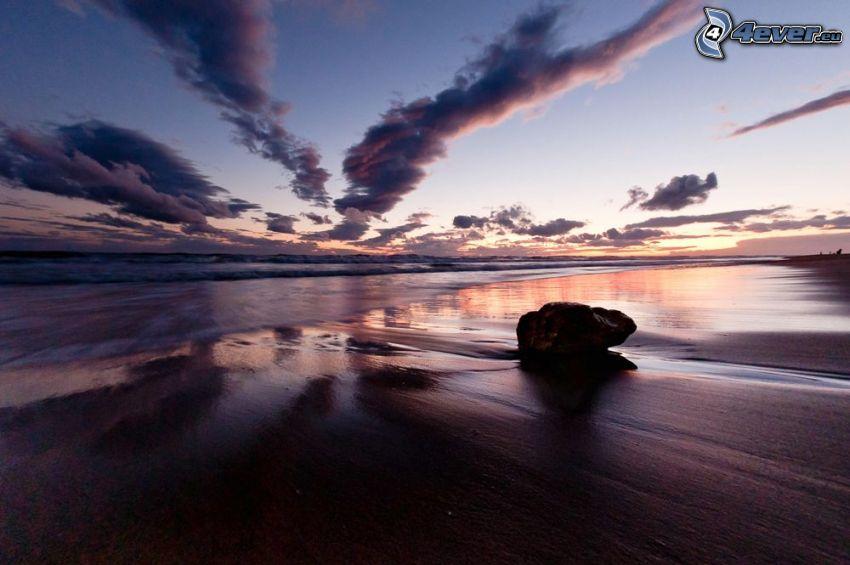 plaża po zachodzie słońca, morze, skała na plaży, fioletowe niebo