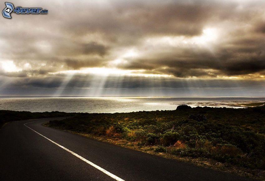 ulica, promienie słońca za chmurami, morze