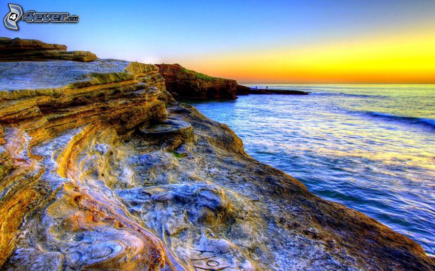 wybrzeże o zachodzie słońca, skalisty brzeg, morze