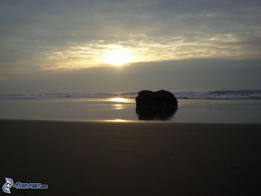 Zachód słońca nad morzem, skała na plaży