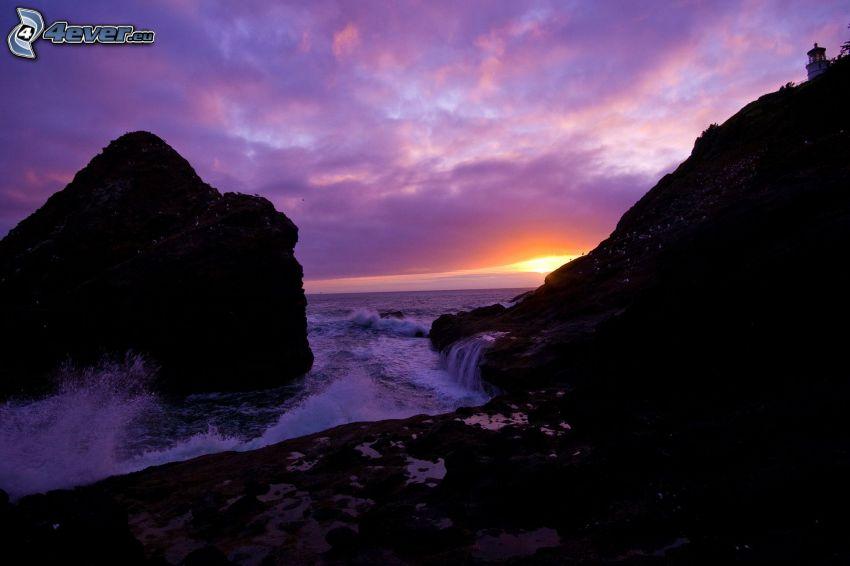 zachód słońca nad morzem, skalisty brzeg, fioletowe niebo