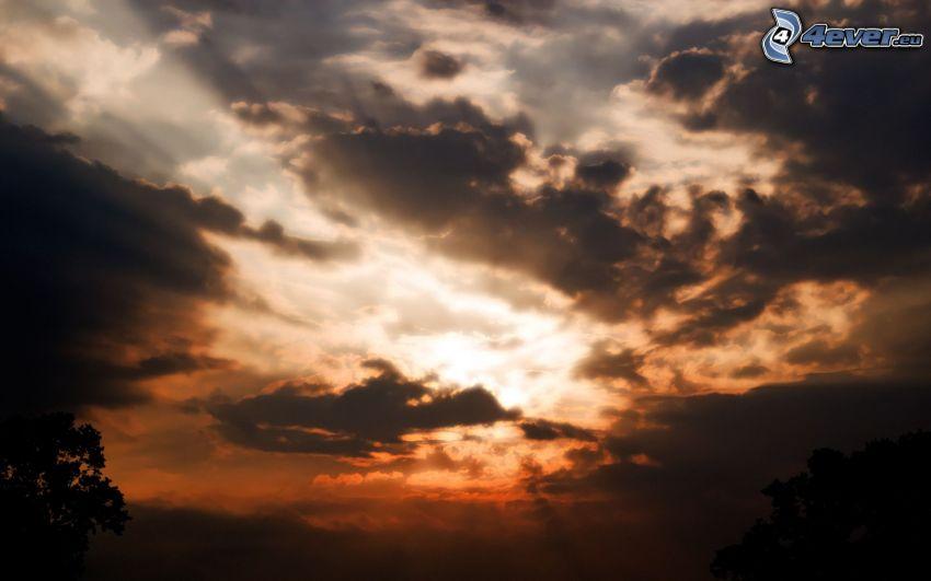 ciemne chmury, promienie słońca za chmurami