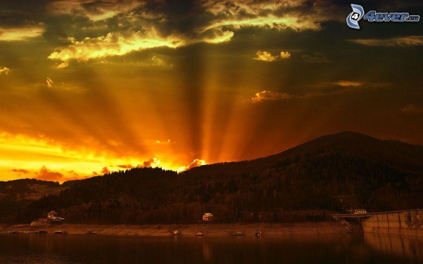 zachód słońca za wzgórzem, pomarańczowy zachód słońca, promienie słoneczne, jezioro