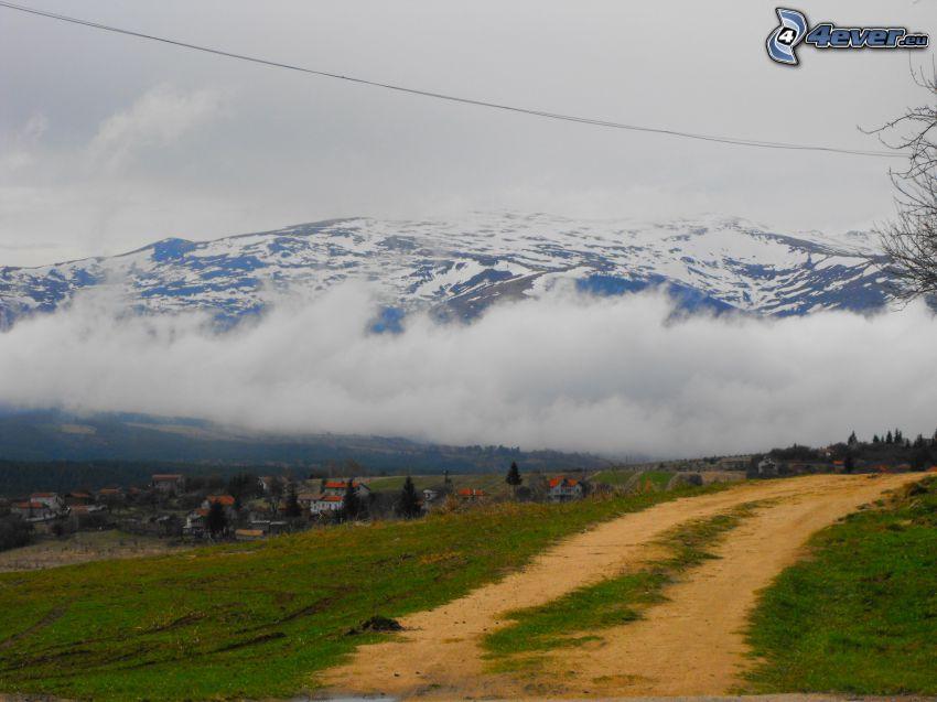 polna droga, chmury, zaśnieżone góry, wioska