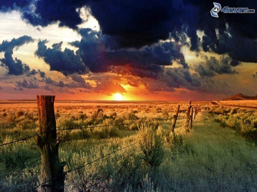 zachód słońca w polu, płot, ciemne chmury