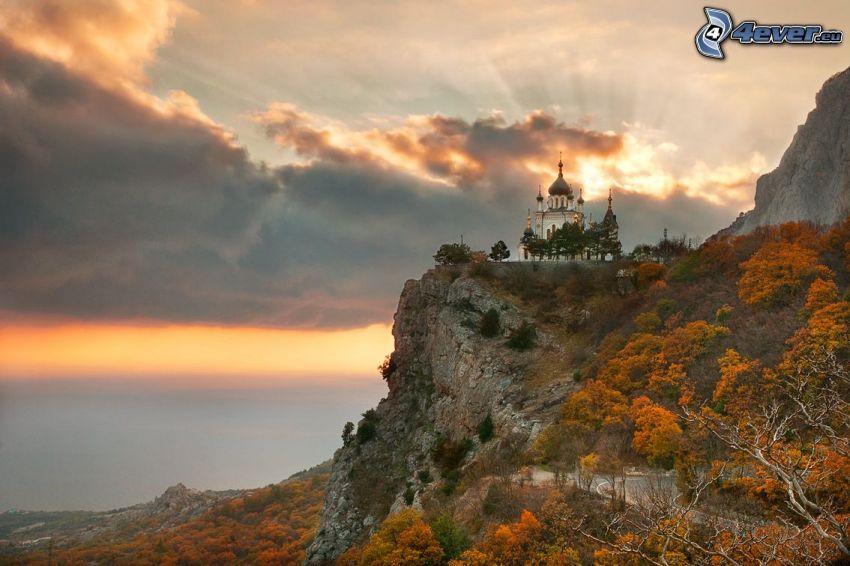 zamek, skała, promienie słońca za chmurami, żółte drzewa