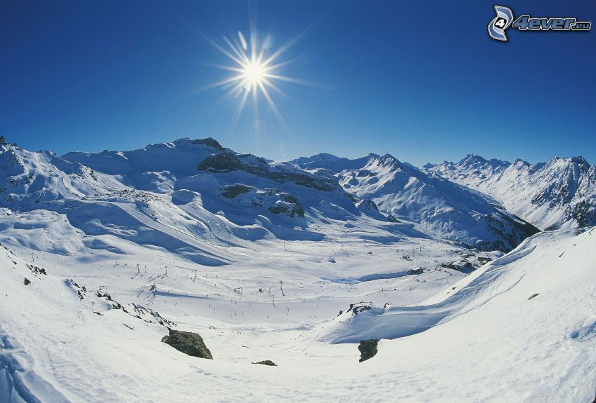 zaśnieżone pasmo górskie, stok, narciarze, słońce