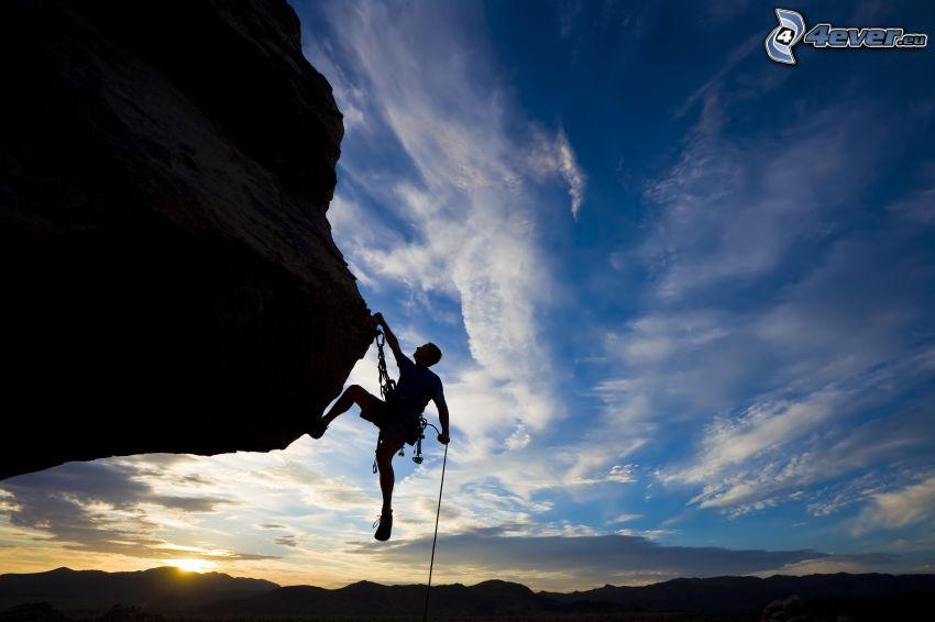 alpinista, skała, zachód słońca za wzgórzem