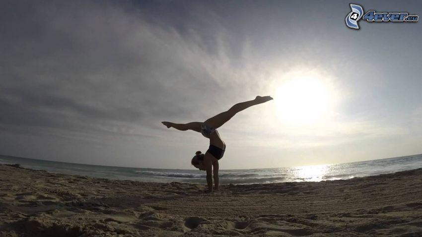 stanie na rękach, szpagat, morze, plaża piaszczysta