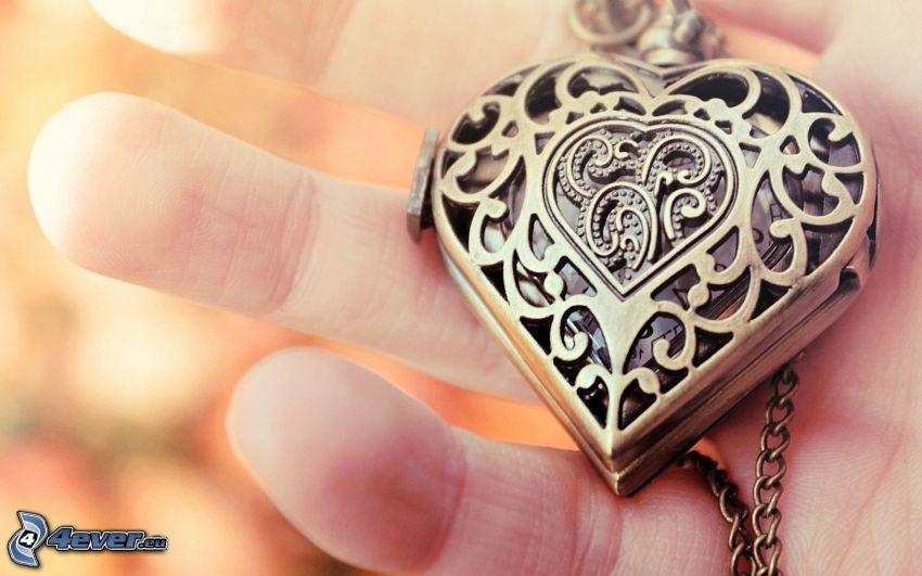 srebrny wisiorek, ręka, serduszko