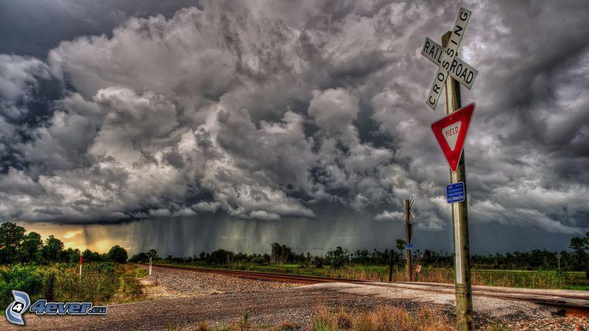 przejazd kolejowy, znak drogowy, ciemne chmury, deszcz
