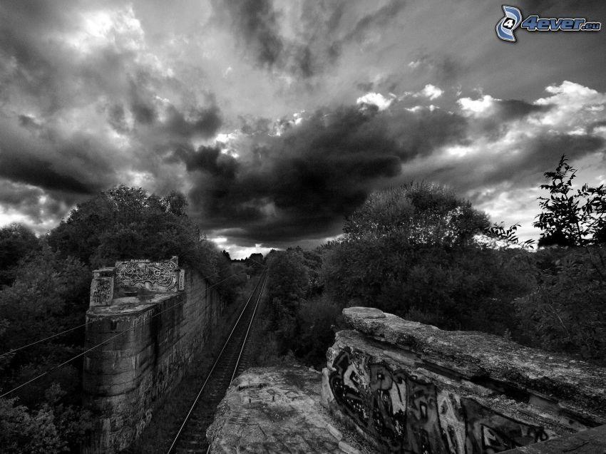 tory kolejowe, skały, las, chmury, czarno-białe zdjęcie