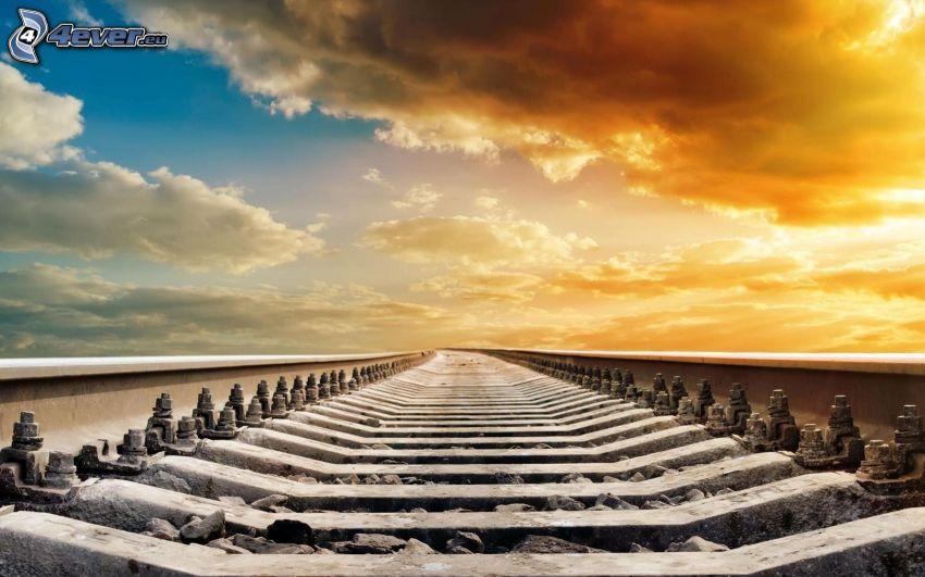 tory kolejowe, słońce za chmurami, żółte niebo