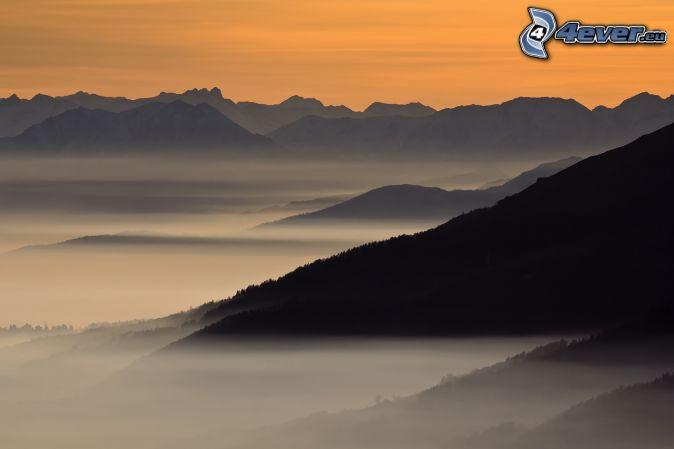 kopce, prízemná hmla, oranžový západ slnka