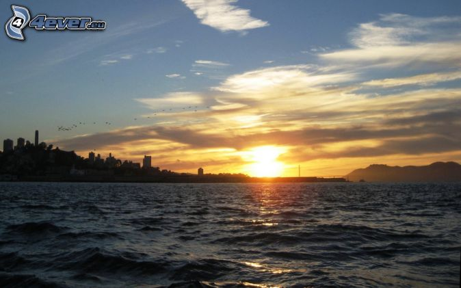 západ slnka za jazerom