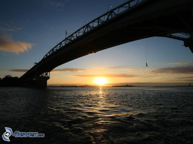 Auckland Harbour Bridge, západ slnka za morom