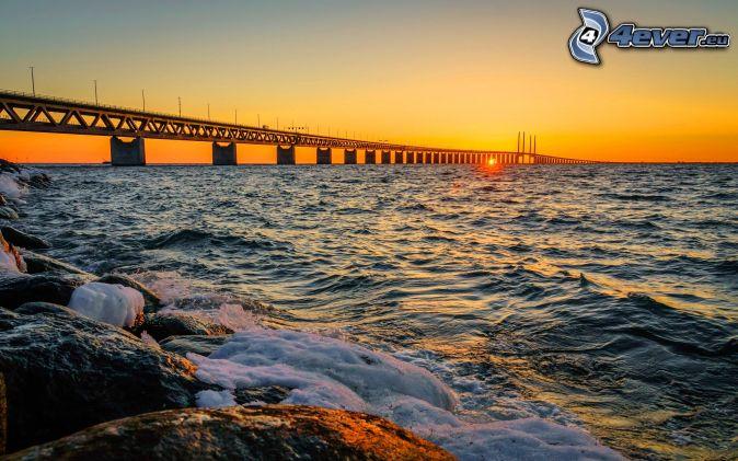 Øresund Bridge, západ slnka za morom, žltá obloha