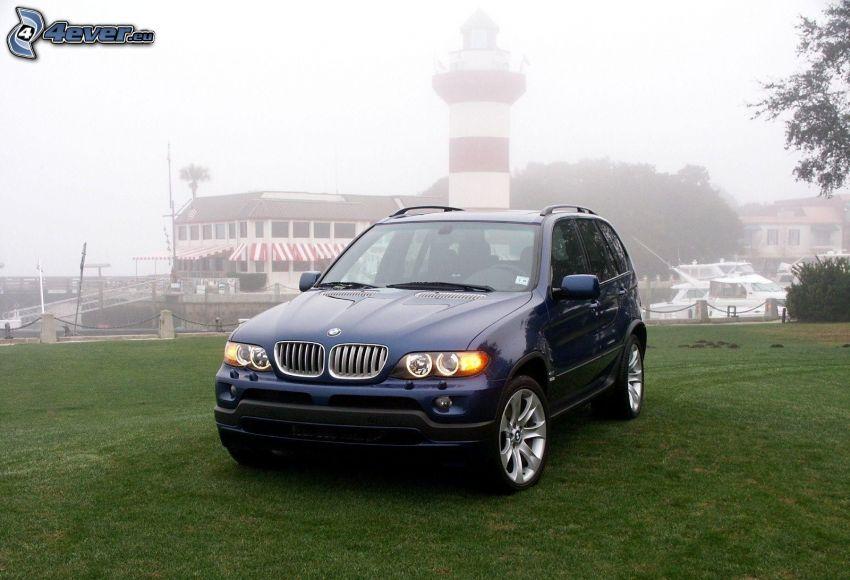 BMW X5, trávnik, maják v hmle