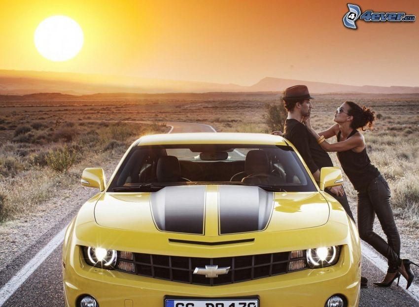 Chevrolet Camaro, predná maska, muž a žena, západ slnka, púšť