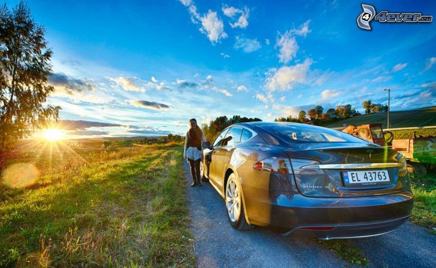 Tesla Model S, elektrické auto, západ slnka za lúkou