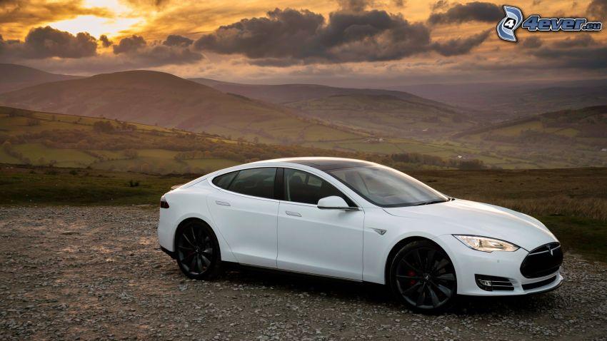 Tesla Model S, pohorie, západ slnka, tmavé oblaky