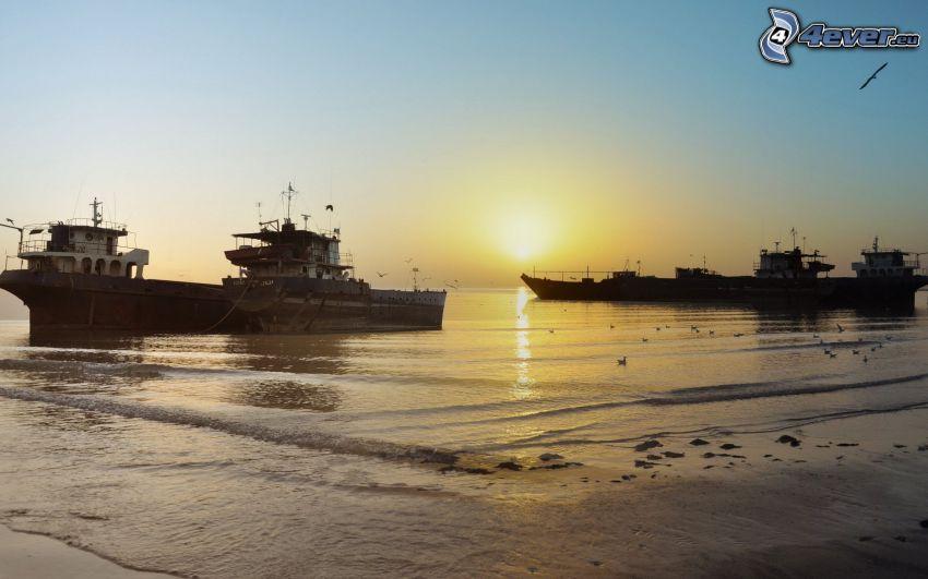 lode, vrak, západ slnka za morom