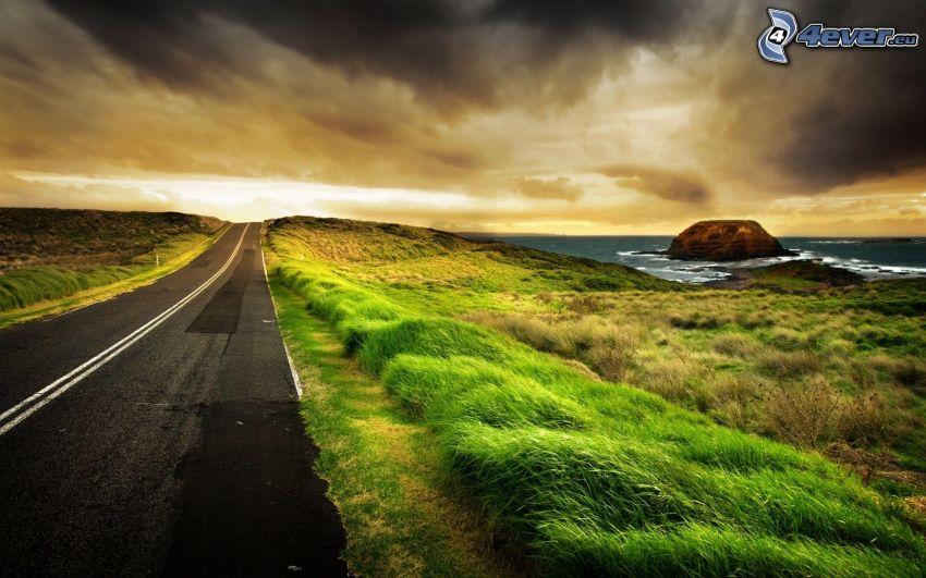 rovná cesta, more, tmavá obloha, tráva