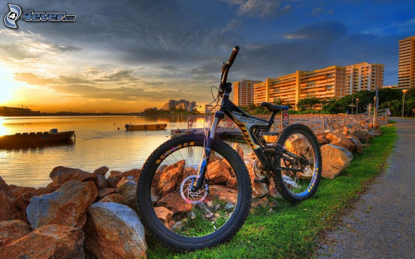 horský bicykel, kamene, západ slnka za jazerom, paneláky, HDR
