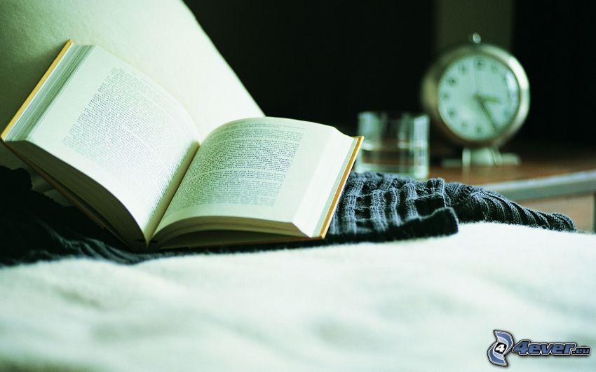 kniha, posteľ, budík