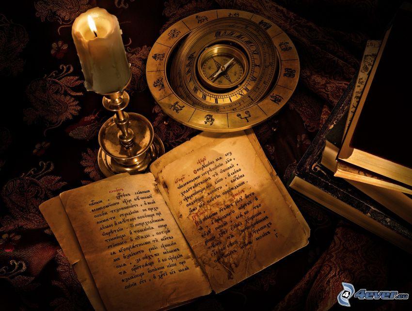 staré knihy, kompas, sviečka