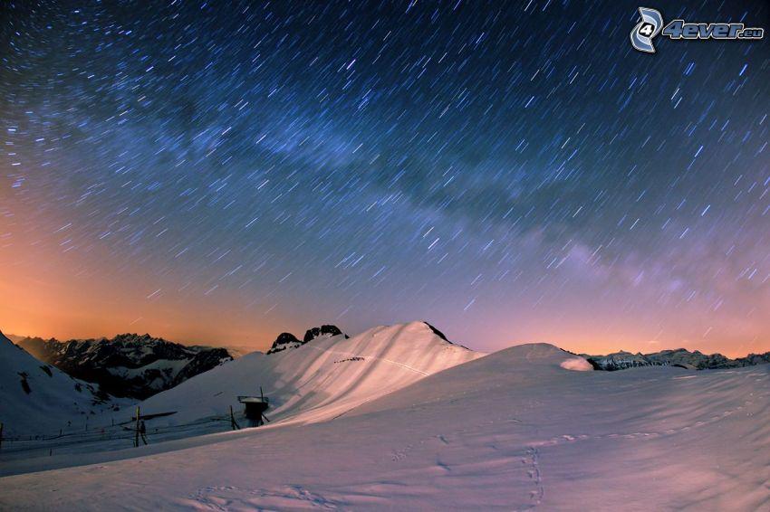 zasnežené kopce, hviezdy, rotácia Zeme