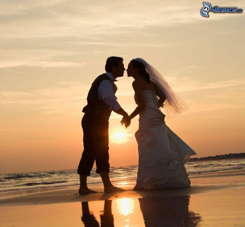 mladomanželia, západ slnka nad plážou