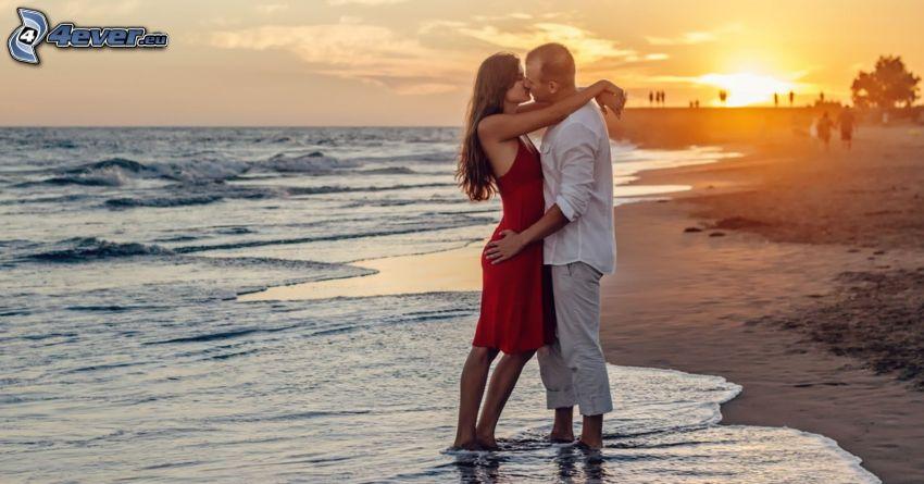 párik pri mori, pusa, západ slnka nad plážou, šíre more