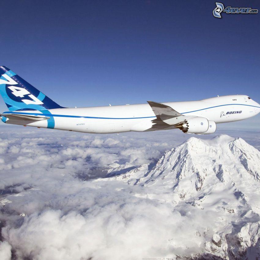 Boeing 747, zasnežené kopce, oblaky, obloha