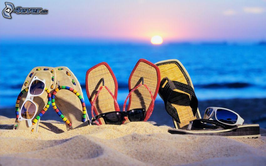 žabky, piesok, slnečné okuliare, západ slnka za morom