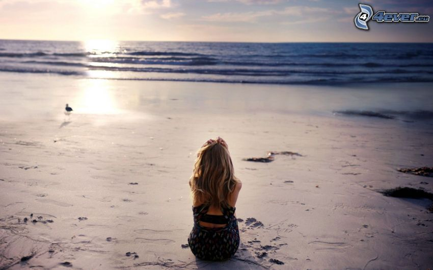 blondínka na pláži, západ slnka za morom, piesočná pláž
