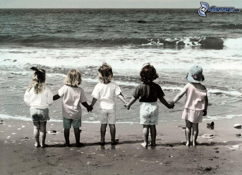 deti, piesočná pláž, more, čiernobiela fotka