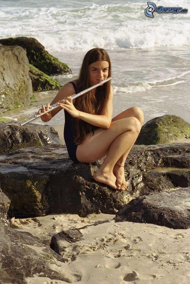dievča na pláži, hra na flaute