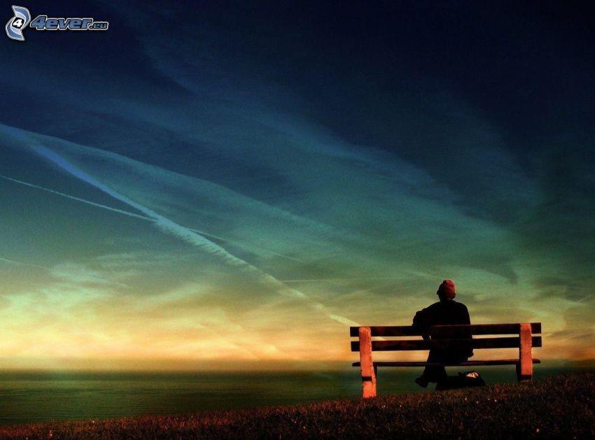 muž na lavičke, pole, výhľad na more, kondenzačné stopy