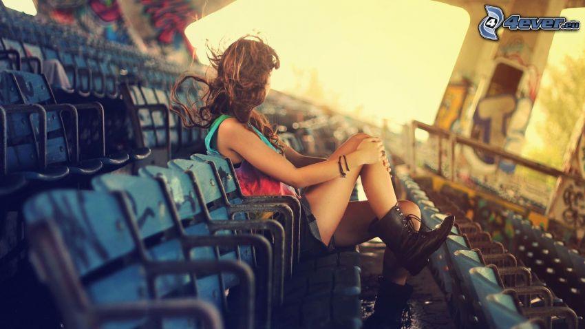 smutné dievča, stoličky, rozlietané vlasy