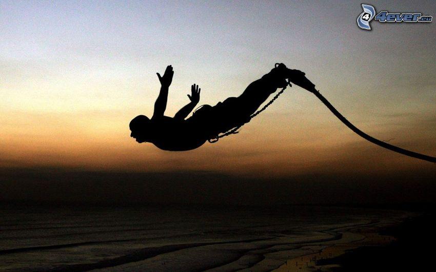 Bungee jumping, silueta chlapa, more, pobrežie, po západe slnka