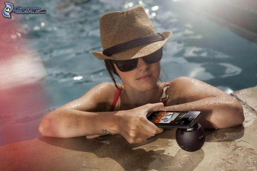 žena v bazéne, mobil, klobúk, slnečné okuliare