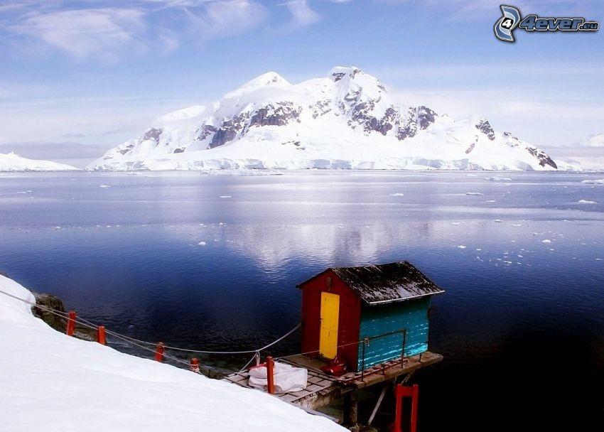 Antarktída, domček, zasnežený skalnatý ostrov, ľadový oceán