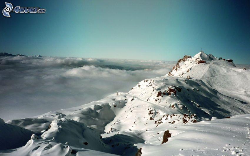 Alpy, zasnežené hory, nad oblakmi